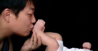 jeune-papa-embrasse-pied-bébé